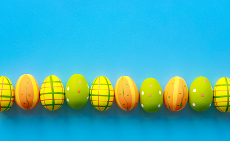 Easter background. Colorful eggs on blue background