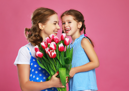 Happy mother's day! child daughter congratulates mother and gives a bouquet of flowers color pink background
