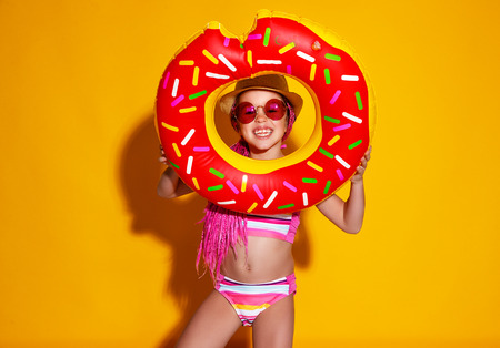 Happy child girl in swimsuit with swimming ring donut on a colored yellow background