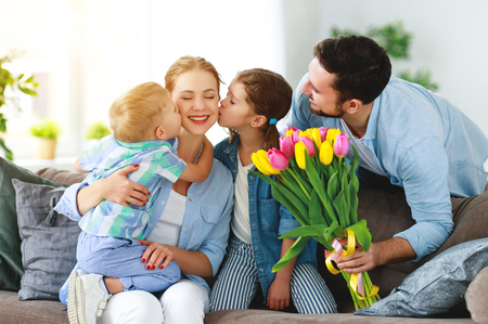 Happy mothers day! father and children congratulate mother on holiday and give flowers