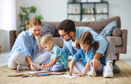 Happy family mother father and kids draw together at a home Stock Photo