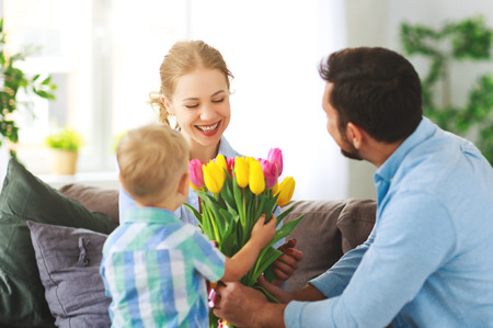 Happy mothers day! father and child son congratulate mother on holiday and give flowers