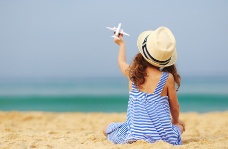 Child girl with toy model airplane on sea on the beach