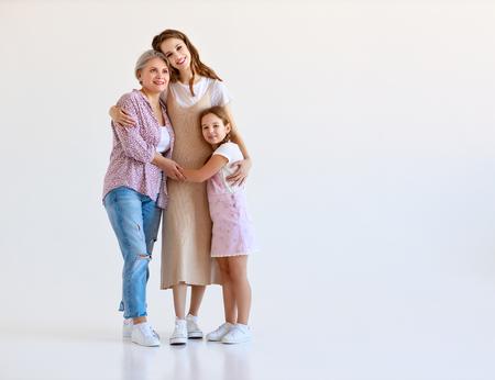 Famille heureuse trois générations grand-mère, mère et enfant sur fond blanc
