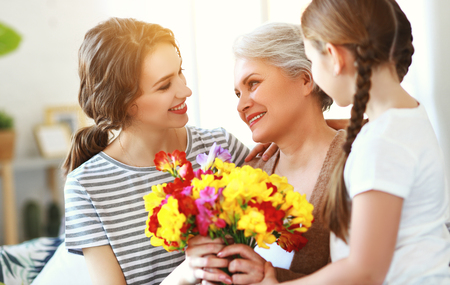 Mothers day! Three generations of a loving family mother, grandmother and daughter congratulate on the holiday, give flowers Banco de Imagens