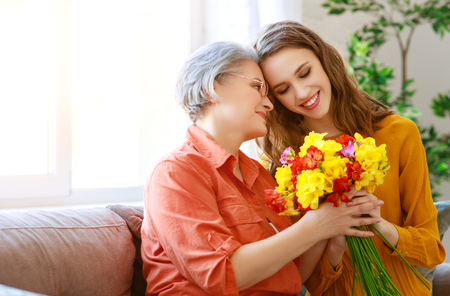 Happy mothers day! Adult daughter gives flowers and congratulates an elderly mother on the holiday