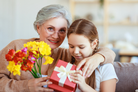Happy mothers day! Granddaughter gives flowers and congratulates an grandmother on the holiday