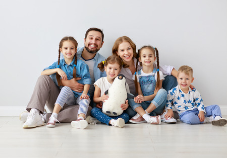Happy large family mother father and children sons and daughters on white background
