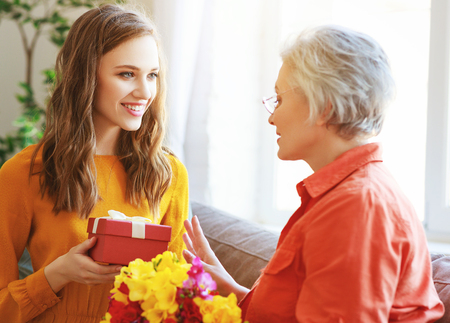 Happy mother's day! An adult daughter gives flowers and congratulates an elderly mother on the holiday