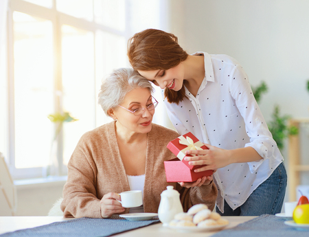 Gelukkige Moederdag! Een volwassen dochter geeft cadeau en feliciteert een bejaarde moeder met de vakantie