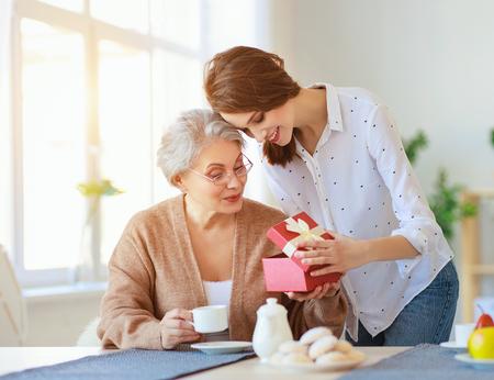 Schönen Muttertag! Eine erwachsene Tochter gibt Geschenk und gratuliert einer älteren Mutter zum Feiertag