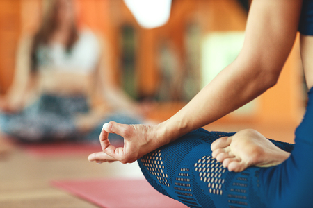 Hand of a woman, mudra, practicing yoga meditating in the Lotus position