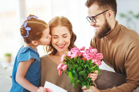 Bonne fête des mères! Le père et la fille de l'enfant félicitent la mère en vacances et donnent des fleurs