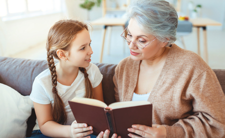 Happy family grandmother reading to granddaughter   child book at home Stockfoto