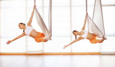 A group of people engaged in a class of yoga Aero in hammocks antigravity Banco de Imagens