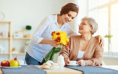 Bonne fête des mères! Une fille adulte donne des fleurs et félicite une mère âgée pour les vacances