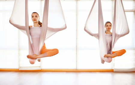 A group of people engaged in a class of yoga Aero in hammocks antigravity Stock Photo