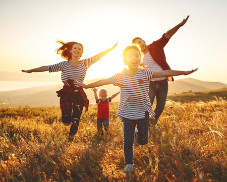 Famiglia felice: madre, padre, figli figlio e figlia sulla natura al tramonto