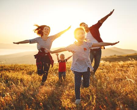Famille heureuse : Mère, père, fils et fille d'enfants sur la nature au coucher du soleil