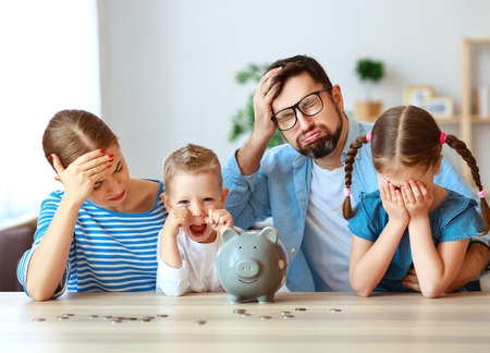 Financial planning despair family mother father and children with piggy Bank bankrupt at home