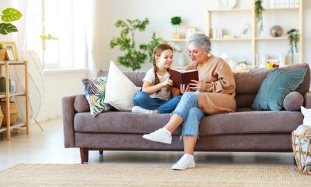 Nonna della famiglia felice che legge al libro del bambino della nipote a casa Archivio Fotografico