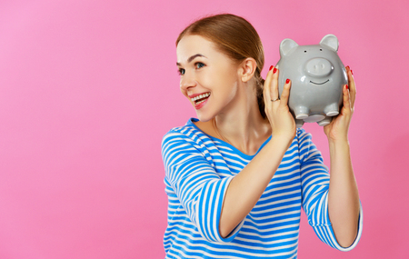 Young happy woman with piggy money bank on pink background. Financial planning concept