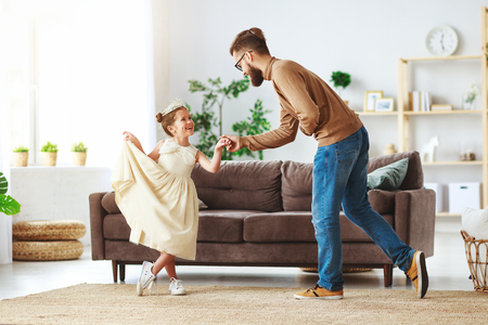 Happy fathers day! Family dad and child daughter Princess dancing at home Stock Photo