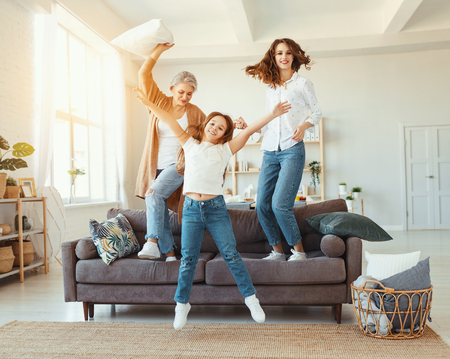 Happy family three generations grandmother, mother and child dancing, jumping and laugh at home Archivio Fotografico