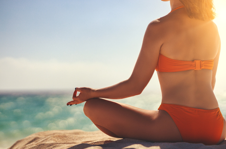 Woman practices yoga and meditates in the lotus position on the beach Stock fotó