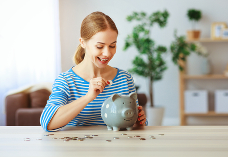 Young happy woman with piggy money at home. Financial planning concept