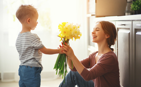 Happy mothers day! Child son congratulates mother on holiday and gives flowers