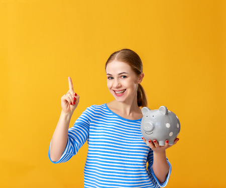 Young happy woman with piggy money bank on yellow background. Financial planning concept