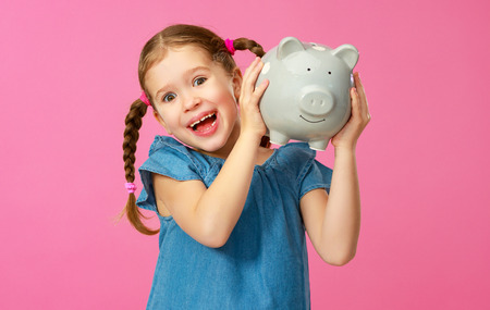 Financial concept of children's pocket money. A child girl with piggy bank on a colored pink background