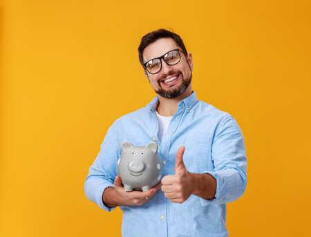 Concept of finance and business. A man with piggy bank on a yellow background