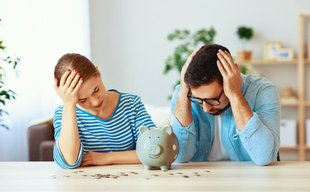 Financial planning bankrupt family couple in stress with piggy bank at home