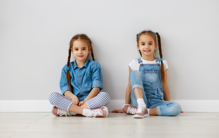 Happy fun kids girls twins at the empty white wall background