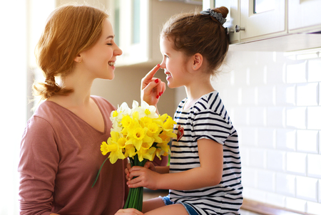 Happy mothers day! child daughter congratulates mother and gives a bouquet of flowers to narcissus and gift