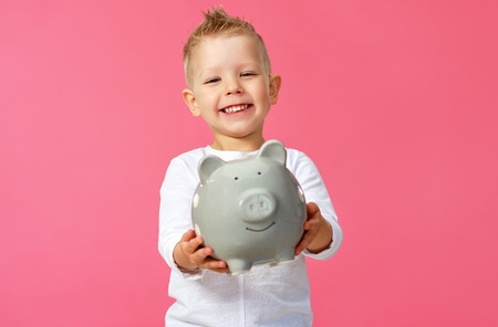 Financial concept of childrens pocket money. A child boy with piggy bank on a colored pink background
