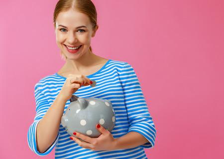 Młoda szczęśliwa kobieta z piggy bank na różowym tle. Koncepcja planowania finansowego