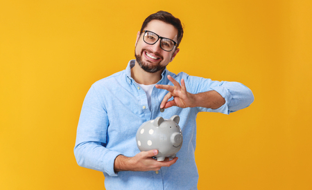 Concept of Finance and business. A man with piggy Bank on a yellow background color Stok Fotoğraf