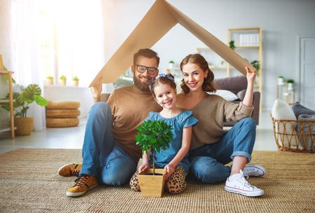 Concetto che ospita una giovane famiglia. Madre, padre e figlio in una nuova casa con un tetto in una casa