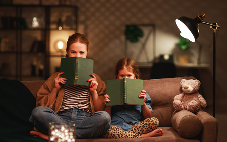 Family before going to bed mother reads to her child daughter book near a lamp in the evening Stok Fotoğraf