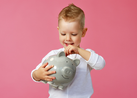 Financial concept of childrens pocket money. A child boy with piggy Bank on a colored pink background Stok Fotoğraf