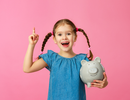 financial concept of childrens pocket money. A child girl with piggy Bank    on a colored pink background Stok Fotoğraf