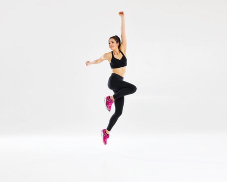 happy young woman doing fitness sports on white background 写真素材