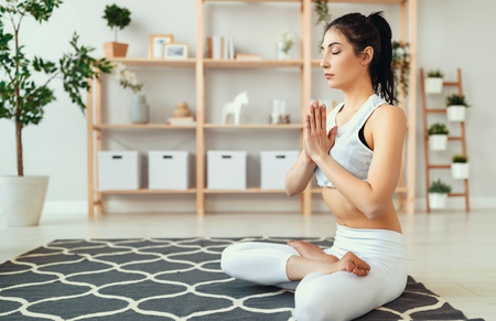young woman doing yoga, meditating in Lotus position at home