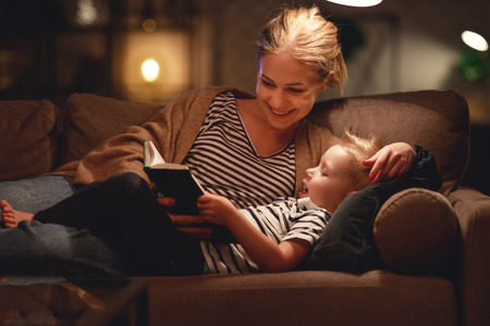 Happy family, before going to bed mother reads to her child son book near a lamp in the evening.