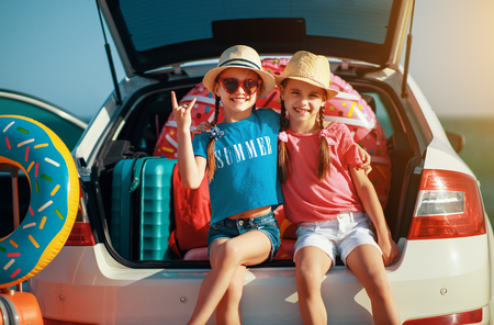 Happy children girls twin sisters on the car ride to the summer trip Stok Fotoğraf