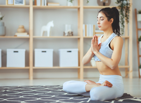 Young woman doing yoga, meditating in Lotus position at home Stok Fotoğraf