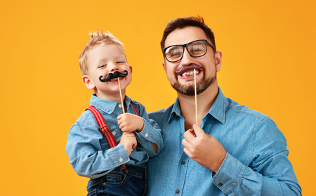 Happy fathers day! funny dad and son with mustache fooling around on colored yellow background